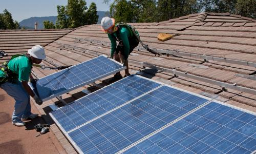 Workers installing rooftop solar panels