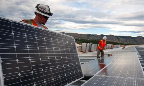Two workers installing rooftop solar panels