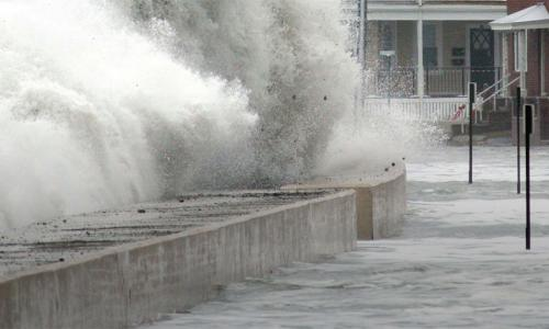 wave breaking on sea wall flooding neighborhood