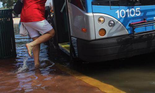 Woman boarding bus in flooded street in Miami, Florida